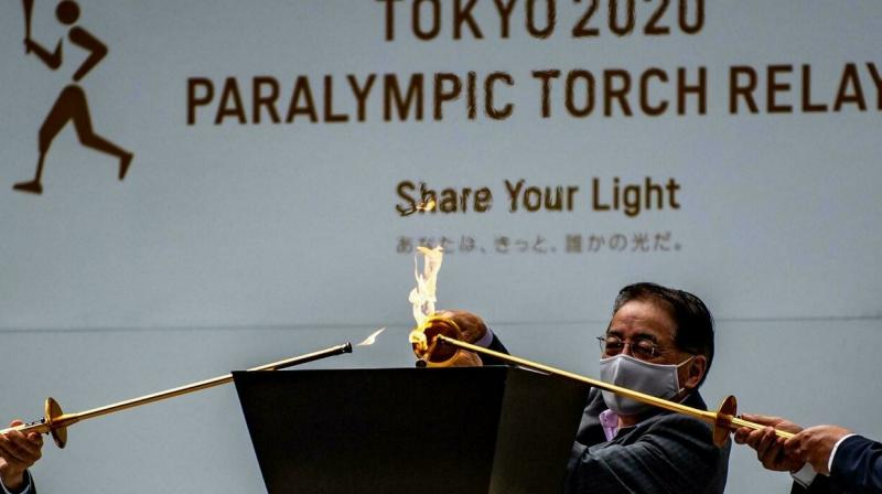 Flame-lighting ceremonies were held without spectators across Tokyo on Friday, after the traditional torch relay was scrapped over fears that crowds could spread infections. (AFP Photo)