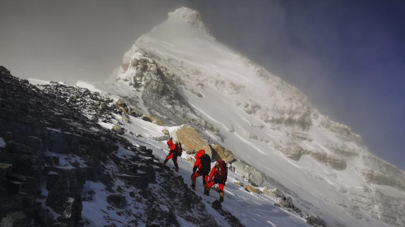 Members of a Chinese surveying team head for the summit of Mount Everest, also known locally as Mt. Qomolangma. China and Nepal have jointly announced on Tuesday, Dec. 8, 2020, a new height for Mount Everest, ending a discrepancy between the two nations. (AP)