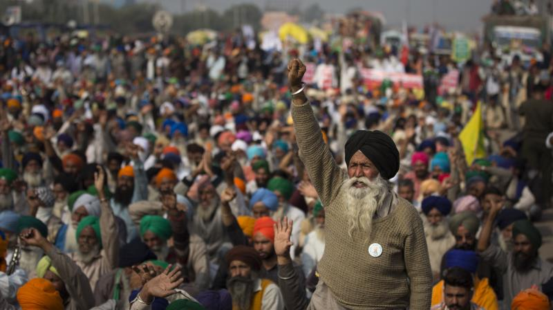 An elderly farmers shouts slogans as others listen to a speaker as they block a major highway during a protest at the Delhi-Haryana state border, India, Tuesday, Dec. 1, 2020. (AP)