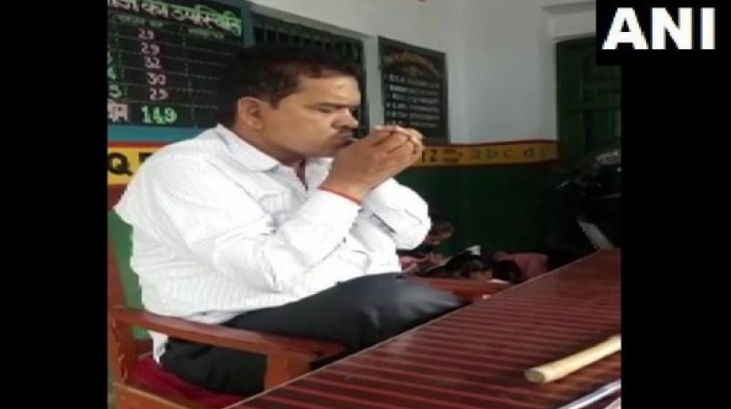 In the video, the teacher was seen lighting and smoking a beedi in front of primary students inside the classroom. (Photo: ANI)
