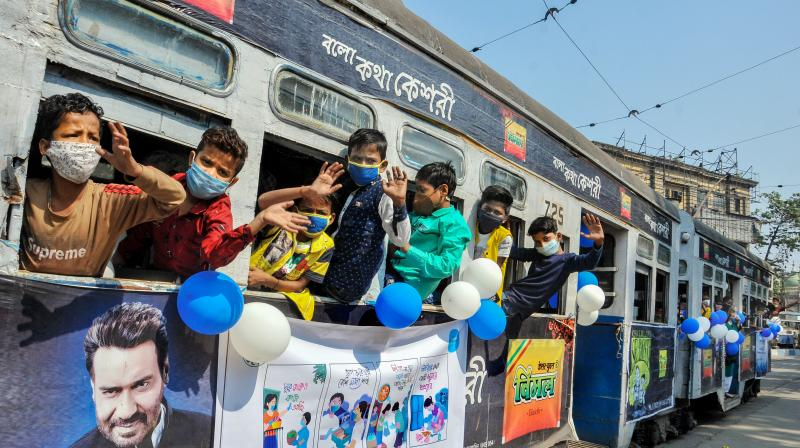 Children wave from a tram during a joy ride in Kolkata, Nov. 14, 2020. (PTI)