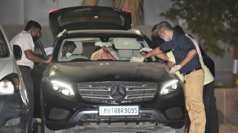 NIA officers investigate Sachin Vaze's Mercedes car following his arrest, in connection with a probe into the recovery of explosives from a car parked near industrialist Mukesh Ambanis house, in Mumbai, Tuesday, March 16, 2021. (PTI/Mitesh Bhuvad)