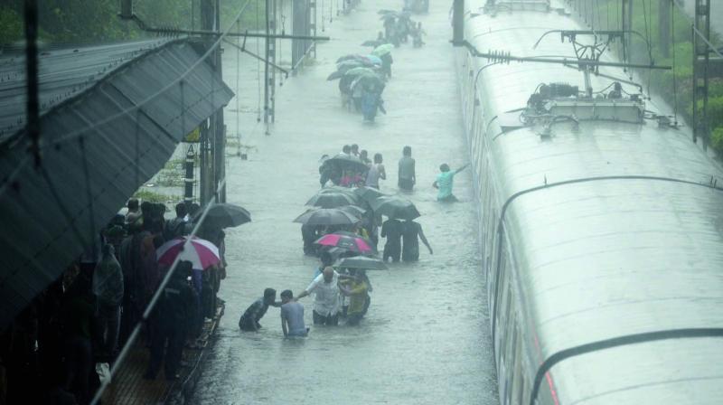 People try to cross flooded railway tracks near Sion station in Mumbai. (Photo: Rajesh Jadhav)