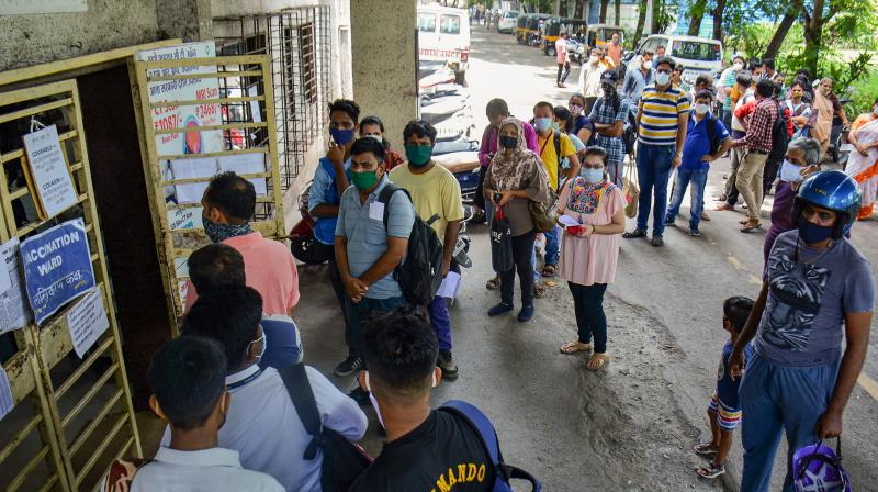 Beneficiaries wait for the COVID-19 vaccine dose outside a vaccination centre at Chhtrapati Shivaji Maharaj hospital in Thane. (Photo: PTI)