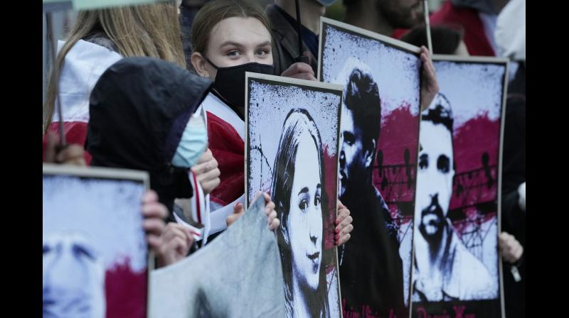 Protesters hold banners and flags during a demonstration demanding freedom for Belarus opposition activist Raman Protasevich, in front of the Belarus embassy in Warsaw, Poland. (Photo: AP)