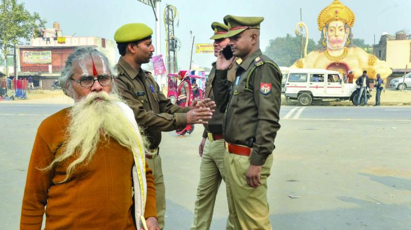 A sadhu walks down a road as police personnel keeps vigil in Ayodhya on Wednesday, the eve of the anniversary of Babri mosque demolition. (Photo: PTI)