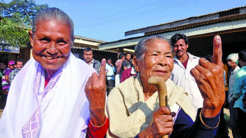 Elderly tribal women show their finger marked with indelible ink after casting vote at a polling station in Kamrup. (Photo: PTI)