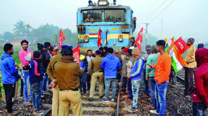 Members of AITUC and INTUC block a train during the trade unions' nationwide strike in West Midnapore, West Bengal, on Wednesday. 	(Photo: PTI)