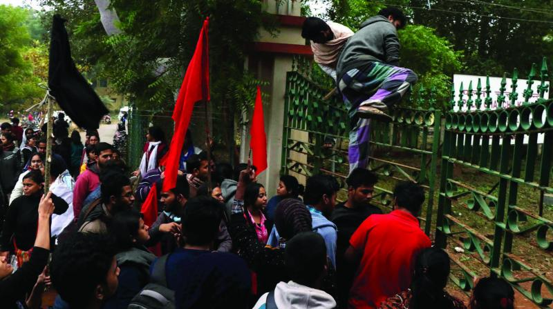 Left-wing students cross the gate to enter as they gherao Rajya Sabha MP Swapan Dasgupta, who was there to deliver a lecture on CAA, at Viswa Bharati University in Birbhum district of West Bengal on Wednesday. (Photo: PTI)