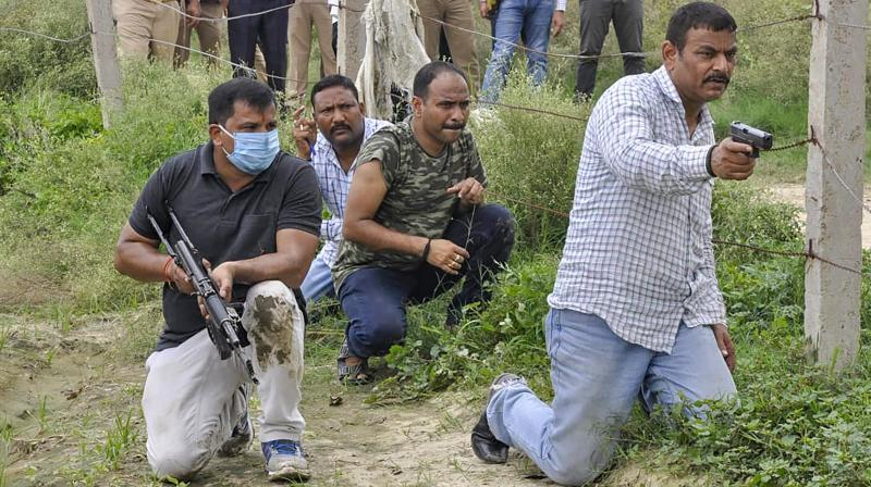 STF and Forensic teams re-enact the events leading to the encounter of slain gangster Vikas Dubey, as part of ongoing investigation of the case, in Kanpur district. PTI photo