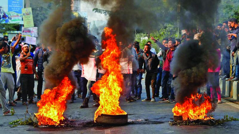 College students burn tyres during the protest against the Citizenship Amendment Bill in Guwahati on Wednesday. (Photo: PTI)