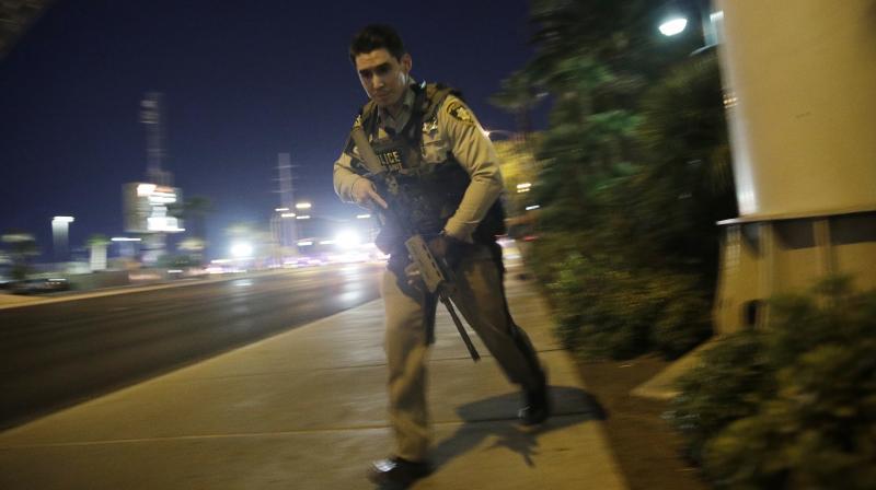 A police officer runs along a sidewalk near a shooting near the Mandalay Bay resort and casino on the Las Vegas Strip, Sunday (Photo: AP)
