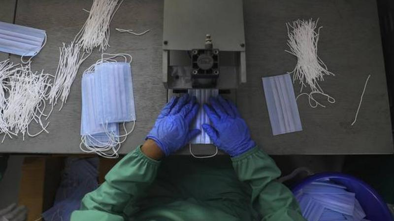 A Central Reserve Police Force soldier stitches a Personal Protective Equipment (PPE) suit for health workers. (Photo: AP/File)