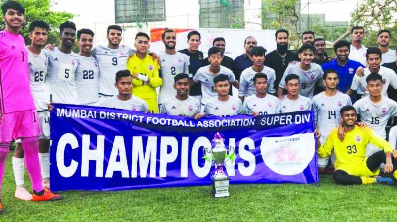 The players, coaches and support staff of FC Pune City are seen in a jubilant mood as they pose with the Super Division title along with Chief Guest, Clarence Lobo, hockey coach and recipient of the Dronacharya Award at the prize distribution at the Neville D'Souza ground, Bandra.