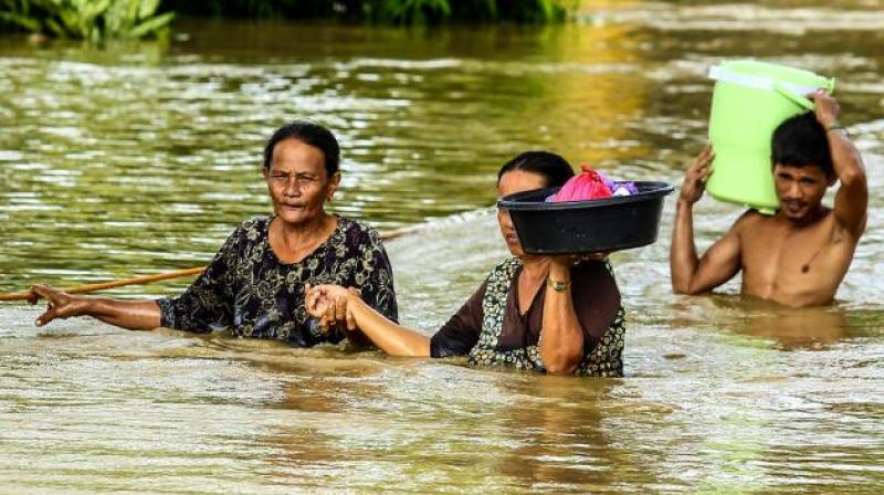 Residents walk through floodwaters as they evacuate to a safer place in Kabacan, North Cotabato, on the southern island of Mindanao. (Photo: AFP)