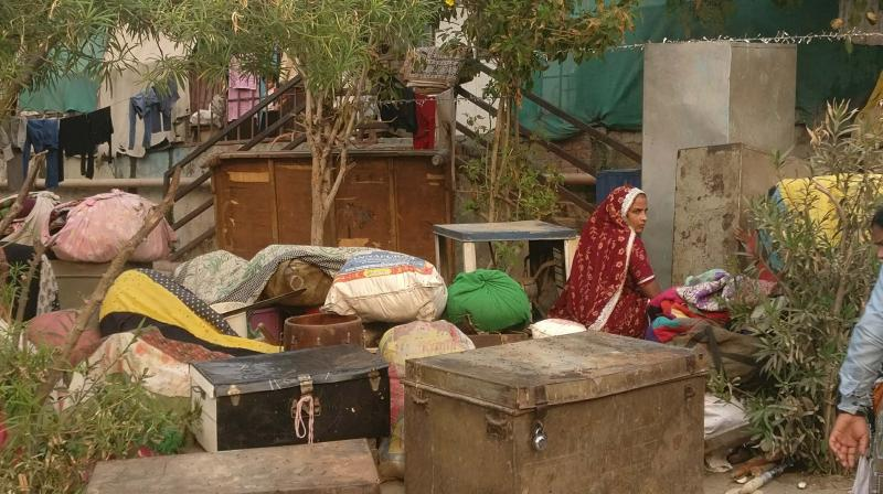 Manju, with her luggage and household items, at a makeshift camp for those displaced from Kathputli Colony.