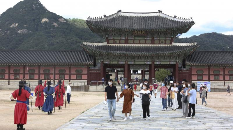 People wearing face masks to help protect against the spread of the coronavirus visit the Gyeongbok Palace in Seoul, South Korea. (AP)