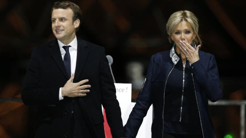 French President-elect Emmanuel Macron holds hands with his wife Brigitte during a victory celebration outside the Louvre museum in Paris. (Photo: AP/File)