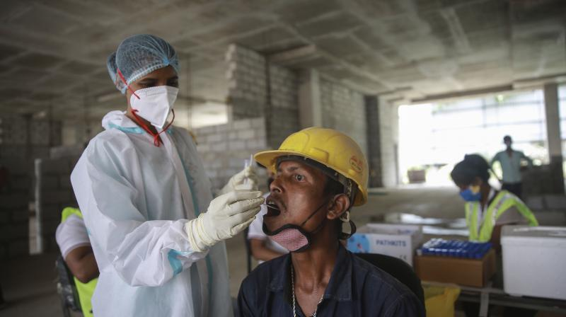A health worker collects a laborer's swab sample at a construction site to test for the coronavirus in New Delhi. (Photo: PTI)