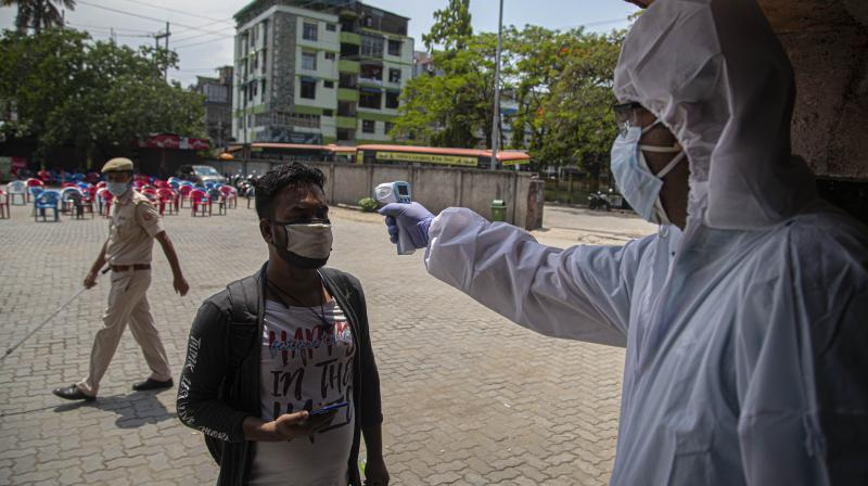 A health worker checks the temperature of a man who arrived to board special buses to their villages in Guwahati. (AP)