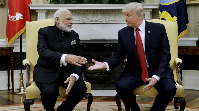 US President Donald Trump reaches to shake hands with with Indian Prime Minister Narendra Modi during their meeting in the Oval Office of the White House in Washington. (Photo: AP)