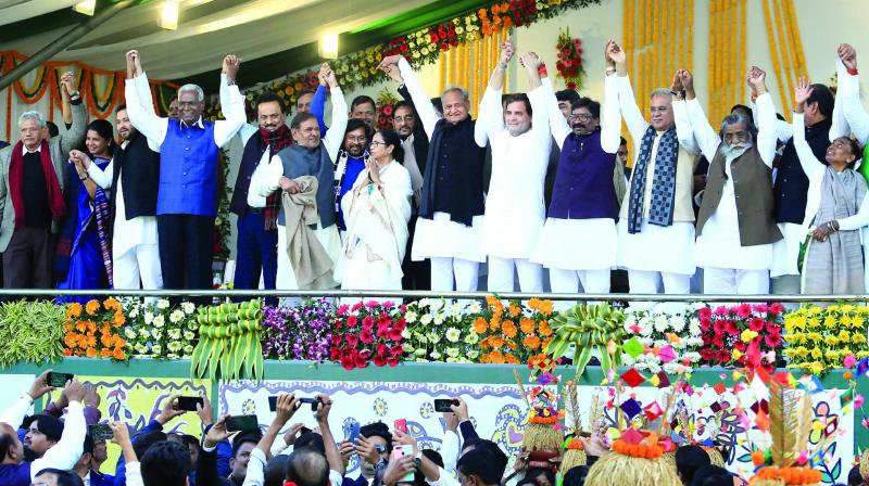 Newly sworn-in Jharkhand chief minister Hemant Soren with his father Shibu Soren, mother Rupi Soren, Congress leader Rahul Gandhi, West Bengal CM Mamata Banerjee, Rajasthan CM Ashok Gehlot, DMK leaders M.K. Stalin and Kanimozhi, Left party leaders Sitaram Yechury and D. Raja, former JD(U) leader Sharad Yadav,  former Assam CM Tarun Gogoi, RJD leader Tejashwi Yadav, Chhattisgarh CM Bhupesh Baghel and other leaders join hands during the oath taking ceremony at Morabadi Ground in Ranchi on Sunday. (Photo: PTI)