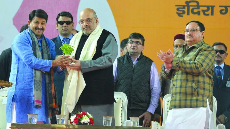 BJP president and Union home minister Amit Shah being presented a sapling by Delhi BJP party president Manoj Tiwari during the BJP booth-level workers' rally, Karyakarta Sammelan, in New Delhi on Sunday. (Photo: Biplab Banerjee)