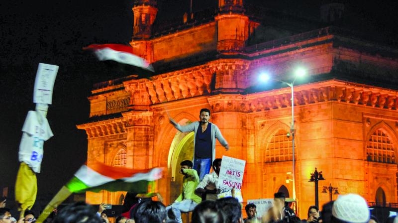 Students protest at the Gateway of India to condemn the attack on the students of JNU, in Mumbai, early Tuesday. (Photo: PTI)