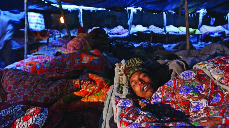 A man sleeps at a night shelter for poor and homeless people, in New Delhi, in the cold morning hours. (Photo: AFP)