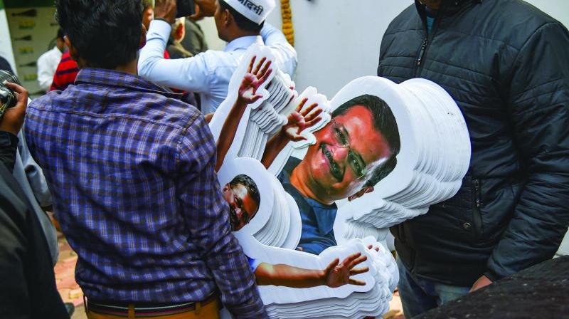 A party worker carries a bundle of chief minister Arvind Kejriwal's cutouts at the AAP office in New Delhi on Tuesday. (Photo: PTI)