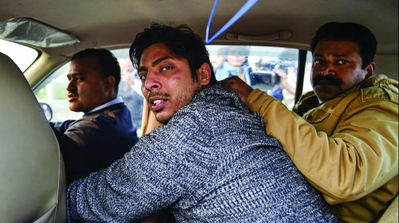 Police take away an unidentified person after he opened fire at Shaheen Bagh in New Delhi on Saturday. (Photo: PTI)