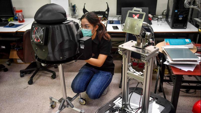 In this photo taken on March 18, 2020 engineering students configure a medical robot modified to screen and observe COVID-19 coronavirus patients at the Regional Center of Robotics Technology at Chulalongkorn University in Bangkok. (Photo | AFP)