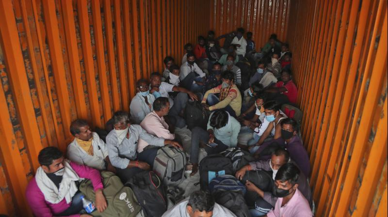 Migrant workers from UP state sit stuffed inside a goods truck on the outskirts of Hyderabad hoping to be driven to their villages in UP. (AP)