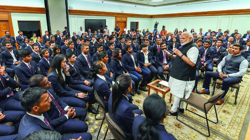 Prime Minister Narendra Modi interacts with medal winners of the 18th Asian Games in New Delhi on Wednesday. Union minister of state for sports Rajyavardhan Singh Rathore is also seen. (Photo: PTI)