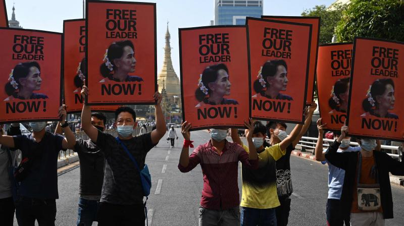 Protesters hold signs calling for the release of detained Myanmar civilian leader Aung San Suu Kyi as they block a road during a demonstration against the military coup in Yangon on February 17, 2021. (Sai Aung Main / AFP)