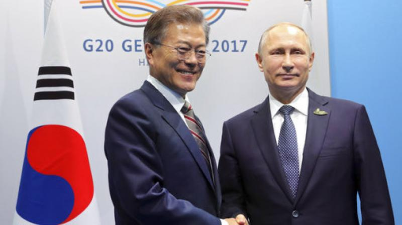 South Korean President Moon Jae-in, left, shakes hands with Russian President Vladimir Putin on the first day of the G-20 summit in Hamburg, Germany. (Photo: AP)