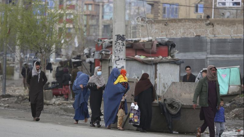 Afghan families leave the site of an attack in Kabul, Afghanistan. AP Photo