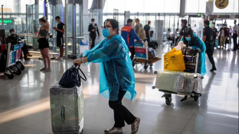 People wearing face masks and plastic overalls, amid concerns over the spread of the COVID-19 coronavirus, walk with their luggage at Suvarnabhumi Airport in Bangkok. AFP Photo
