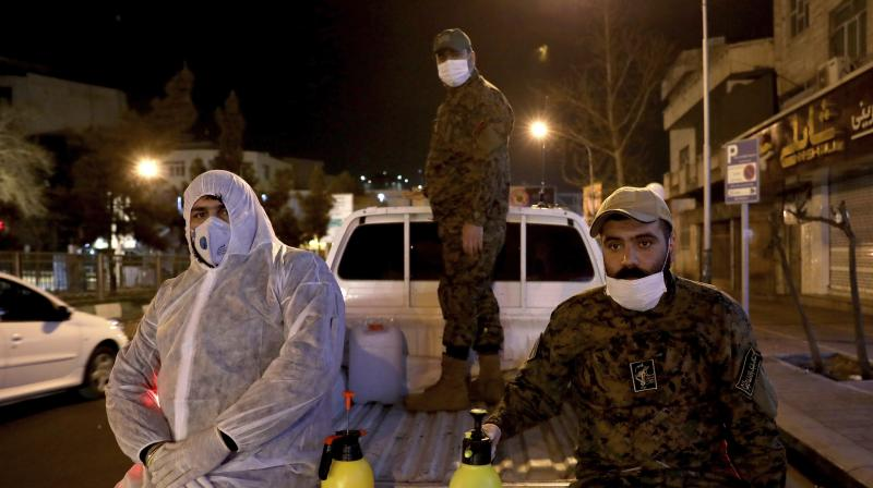 Revolutionary Guard members take part in disinfecting the city to help prevent the spread of the new coronavirus in Tehran, Iran.AP Photo