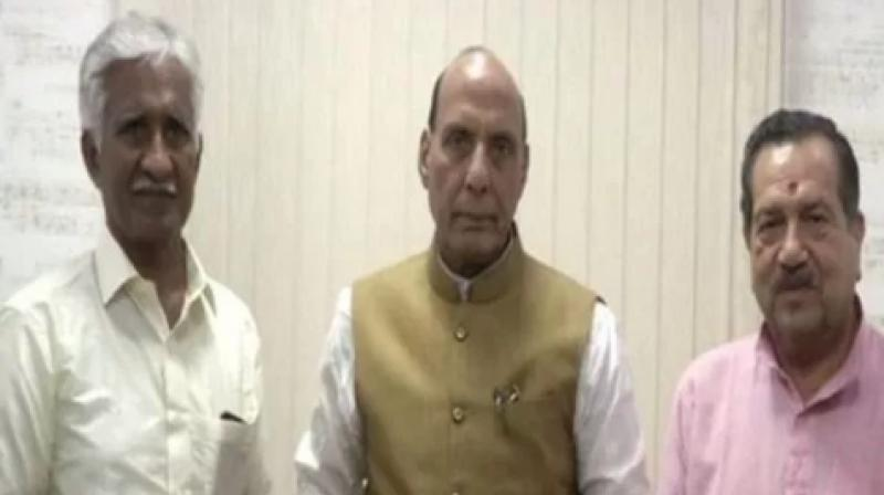 Union Defence Minister Rajnath Singh met Airman C B R Prasad on Monday and received the cheque from him. (Photo: ANI)