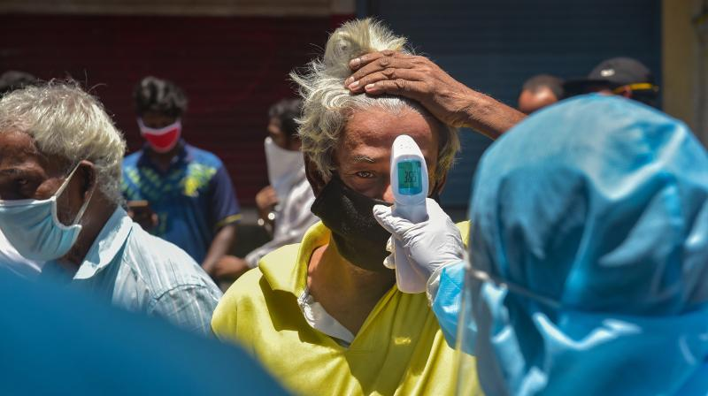 Health workers conduct thermal screening at a locality in Mumbai. (PTI photo)
