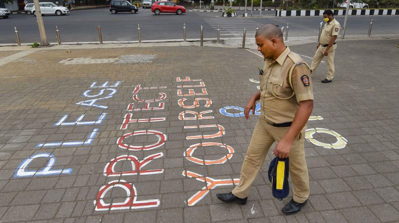 A mumbai police personnel walks past a painted message at Marine drive in Mumbai. PTI photo