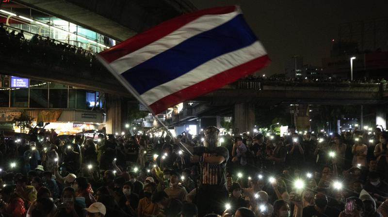 Pro-democracy protesters wave Thailand's national flag as others shine their mobile phone lights during an anti-government protest in Bangkok, Thailand. (AP)