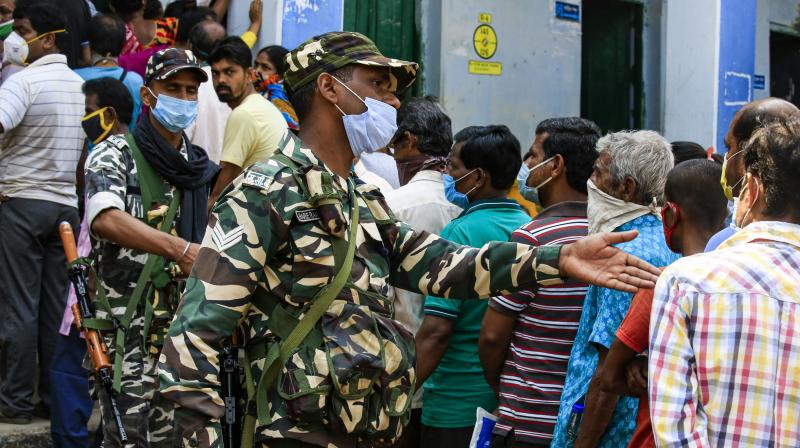Paramilitary soldiers manage a queue at a polling booth during third phase of West Bengal state elections. (AP)