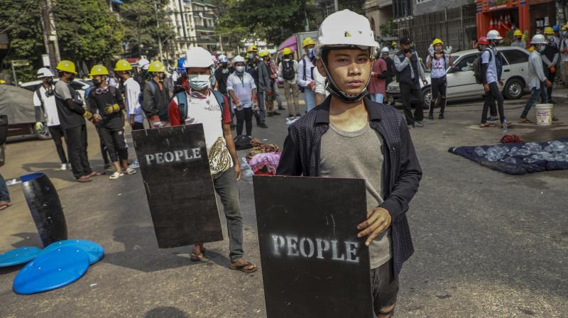 Anti-coup protesters with makeshift shields stand in Yangon, Myanmar on March 3, 2021. (AP)
