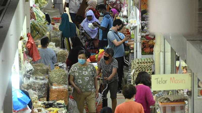 People, wearing face masks as a preventive measure against the spread of the COVID-19 novel coronavirus, shop for food items in the Geylang Serai market in Singapore. AFP photo