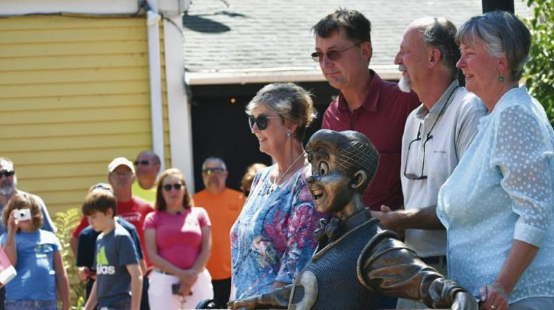 A statue of the comic strip character Archie sits on a park bench, created by sculptor Valery Mahuchy, as it was unveiled in Community Park, Meredith, Thursday, Aug. 9, 2018, as part of the town's 250th anniversary celebration. Archie illustrator Bob Montana lived in Meredith for 35 years and worked many local residents and scenes into the comic strip until his death in 1975 at age 54. Posing with the statue are Montana's children, Paige, Donald, Raymond, and Lynn. (Photo: AP)