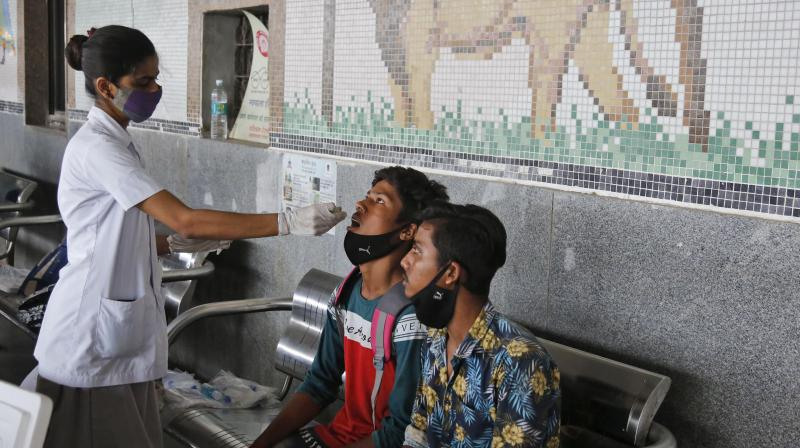 A health worker takes a swab sample of a passenger entering the city to test for COVID-19, at a railway station in Ahmedabad, India. (AP)