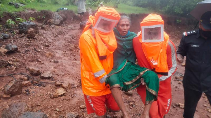 This photograph provided by India's National Disaster Response Force (NDRF) shows NDRF personnel rescuing an elderly woman in Satara, in the western Indian state of Maharashtra, Friday, July 23, 2021. (AP)
