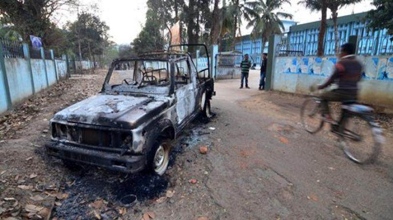 A burnt out Meghalaya Police vehicle is seen in front of community health centre. (Photo: PTI)